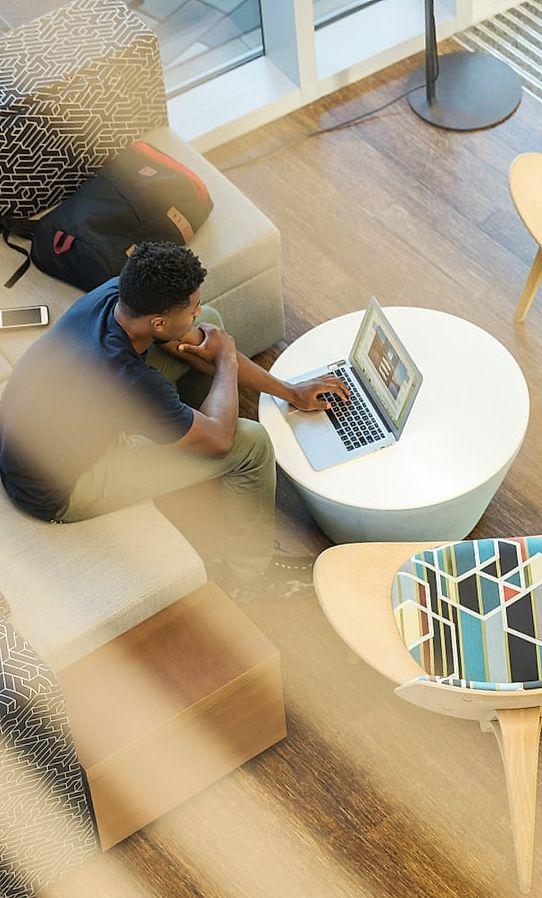 Jonge man zit aan bureau en surfen op internet