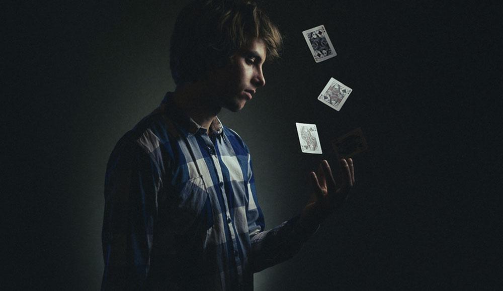 Een man in een donkere achtergrond gooit kaarten