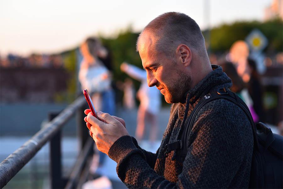 Een man kijkt naar zijn mobiele telefoon