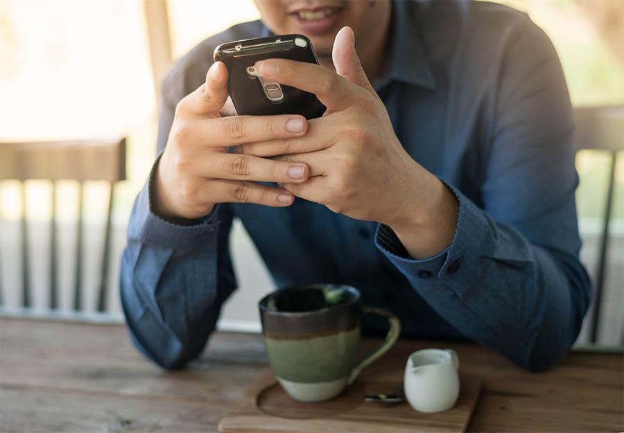 Een man zit aan zijn bureau en kijkt naar zijn telefoon